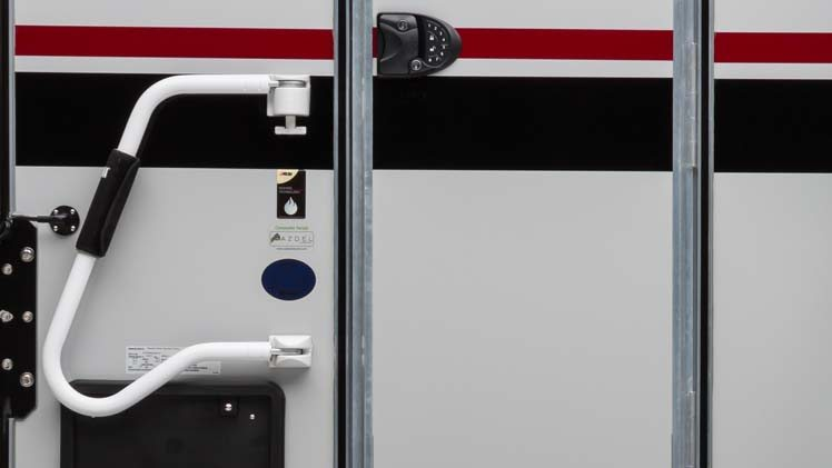Swing out entry assist handle on exterior of truck camper